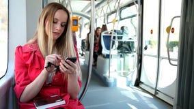 Красивый белокурый трамвай катания женщины, печатая на черни, телефон, клетка, держа стекла акции видеоматериалы