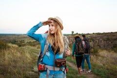 Красивый белокурый усмехаться девушки, смотря в расстояние, предпосылка туристов друзей Стоковые Фото