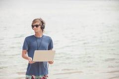 Красивый белокурый человек работая с компьтер-книжкой и наушниками на пляже стоковое изображение