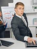 Красивый бизнесмен высчитывая на калькуляторе Стоковое фото RF