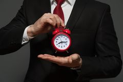 Красивый бизнесмен в официально костюме держа часы Стоковые Изображения