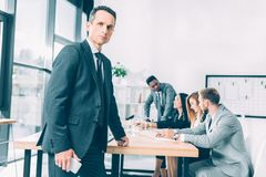красивый бизнесмен в положении костюма в конференц-зале с multiracial коллегами стоковое изображение rf