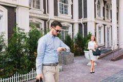 Красивый бизнесмен в солнечных очках смотря дозор на улице Милая элегантная белокурая девушка ждет его дальше стоковое фото