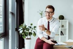 красивый бизнесмен в eyeglasses держа smartphone и указывать стоковое изображение