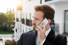 Красивый бизнесмен говоря на городе телефона внешнем Стоковое Изображение RF