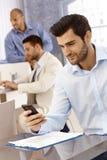 Красивый бизнесмен используя мобильный телефон стоковые фото