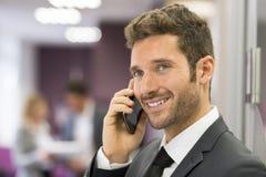 Красивый бизнесмен на мобильном телефоне в современном офисе Стоковые Фото
