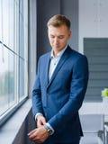 Красивый бизнесмен около окна на запачканной предпосылке владение домашнего ключа принципиальной схемы дела золотистое достигая н стоковые изображения