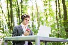 Красивый бизнесмен при шлемофон сидя на столе офиса с портативным компьютером и чашкой кофе в руках в центре телефонного обслужив Стоковая Фотография RF
