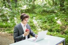 Красивый бизнесмен при шлемофон сидя на столе офиса с портативным компьютером и чашкой кофе в руках в центре телефонного обслужив Стоковое Фото