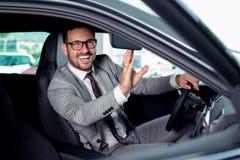 Красивый бизнесмен сидит в новом автомобиле в автосалоне Стоковые Изображения RF