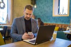 Красивый бизнесмен сидит в современной кофейне с умными телефоном и компьтер-книжкой и наслаждается его кофе утра стоковые изображения rf