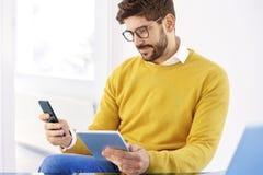 Красивый бизнесмен сидя в офисе и используя сотовый телефон стоковое изображение rf