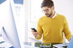 Красивый бизнесмен сидя в офисе и обмене текстовыми сообщениями дальше стоковые фото