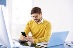 Красивый бизнесмен сидя в офисе и обмене текстовыми сообщениями дальше стоковые изображения