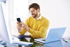 Красивый бизнесмен сидя в офисе и обмене текстовыми сообщениями дальше стоковые изображения rf