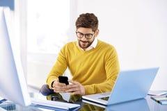 Красивый бизнесмен сидя в офисе и обмене текстовыми сообщениями дальше стоковое изображение