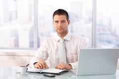 Красивый бизнесмен сидя на столе в офисе стоковые фото