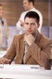 Красивый бизнесмен сидя на столе Стоковые Изображения