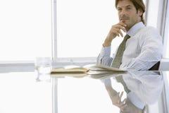 Красивый бизнесмен сидя на столе переговоров Стоковые Изображения RF