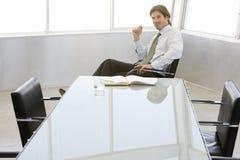 Красивый бизнесмен сидя на столе переговоров Стоковое Изображение