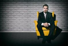 Красивый бизнесмен сидя самостоятельно на кресле в пустой комнате Стоковое фото RF