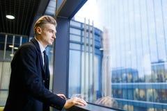 Красивый бизнесмен смотря вне окно Стоковое Изображение