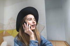 Красивый битник девушки говоря на телефоне в комнате и улыбках Портрет девушки которая говорит телефоном Стоковые Изображения RF