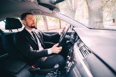 Красивый бородатый бизнесмен управляя автомобилем на дороге стоковая фотография