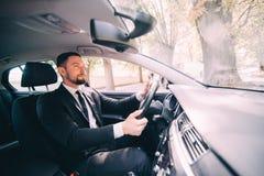 Красивый бородатый бизнесмен управляя автомобилем на дороге стоковое изображение