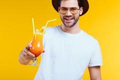 красивый бородатый молодой человек в шляпе и солнечных очках держа стекло коктеиля лета и усмехаясь на камере Стоковая Фотография RF