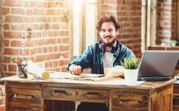 Красивый бородатый мужской архитектор работая на плане здания стоковое фото