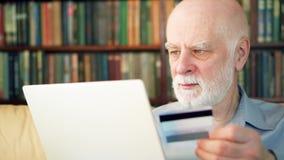 Красивый бородатый старший человек сидя дома Ходить по магазинам он-лайн с кредитной карточкой на компьтер-книжке видеоматериал