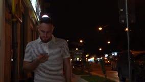 Красивый бородатый человек идя вечером улица и используя его мобильный телефон Насладитесь прогулкой ночи видеоматериал