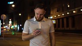 Красивый бородатый человек идя вечером улица и используя его мобильный телефон Насладитесь прогулкой ночи акции видеоматериалы