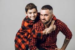 Красивый бородатый человек и мальчик на его назад смотрят камеру стоковая фотография rf