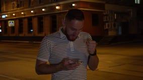 Красивый бородатый человек получает текстовое сообщение или sms и он очень счастливы о нем Гай в striped выигрыше поло сток-видео