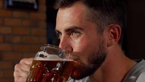Красивый бородатый человек усмехаясь joyfully пока выпивающ пиво акции видеоматериалы