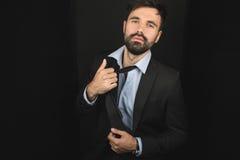 Красивый бородатый бизнесмен представляя в связи и черном костюме стоковое изображение rf