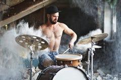 Красивый бородатый парень играет барабанчики стоковое фото rf