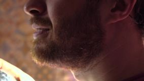 Красивый бородатый человек распыляя некоторый дух на его шеи Съемка замедленного движения, взгляд конца-вверх профиля видеоматериал