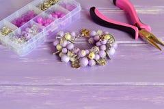 Красивый браслет с сиренью и белыми пластичными шариками, цветками металла и листьями Стоковое Изображение RF