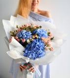 Красивый букет владением женщины голубых цветков гортензии и розовых роз на белизне Стоковые Изображения RF