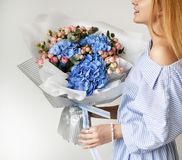 Красивый букет владением женщины голубых цветков гортензии и розовых роз на белизне Стоковые Фотографии RF