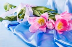 Красивый букет нежных розовых тюльпанов лежа на голубом fabr сатинировки Стоковые Фото