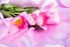 Красивый букет нежных розовых тюльпанов лежа на розовом fabr сатинировки Стоковое Изображение RF