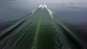 Красивый верхний воздушный взгляд трутня 4k на малой белой роскошной яхте моторной лодки плавая прочь медленно в спокойной речной сток-видео