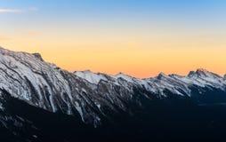 Красивый взгляд захода солнца снега покрыл скалистые горы на Na Banff стоковые фотографии rf