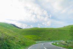 Красивый взгляд ландшафта острословия проселочной дороги и зеленой травы Стоковое Изображение