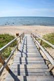 Красивый взгляд лета Балтийского моря, песчаного пляжа, следа деревянных планок и яркого голубого неба Стоковое Изображение